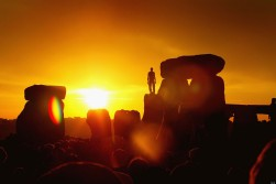 STONEHENGE, ENGLAND - JUNE 21: A reveller greets the sun as it rises above Stonehenge on the day of the Summer Solstice June 21, 2003 in Wiltshire, England. More than 30,000 people danced as they greeted the sunrise on summer?s longest day at Stonehenge. Scholars believe the ring of 20-ton stones was built between 3,000 and 1,600 BC as a sacred temple. (Photo by Scott Barbour/Getty Images)